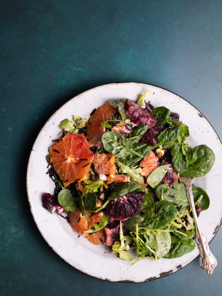 vibrant orange salad on a blue backdrop with wild rice and vegan feta cheese crumbles.