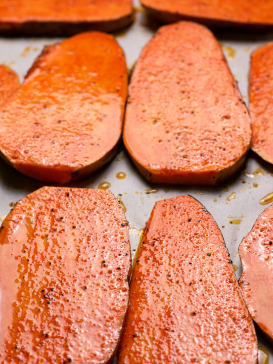Slices of sweet potato on a roasting pan before baking. showing the direciton to slice the sliders.