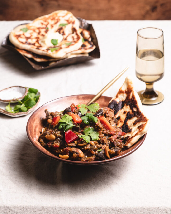 table of indian food with lentil curry and naan
