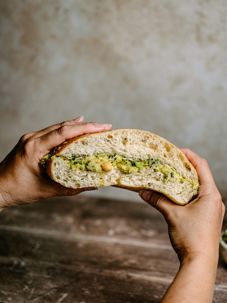 Holding a big vegan sandwich with broccoli sprouts