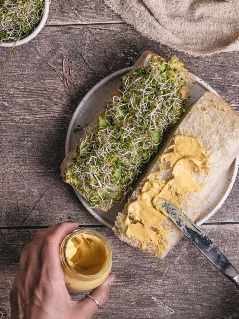 spreading mustard on a chickpea avocado salad sandwich