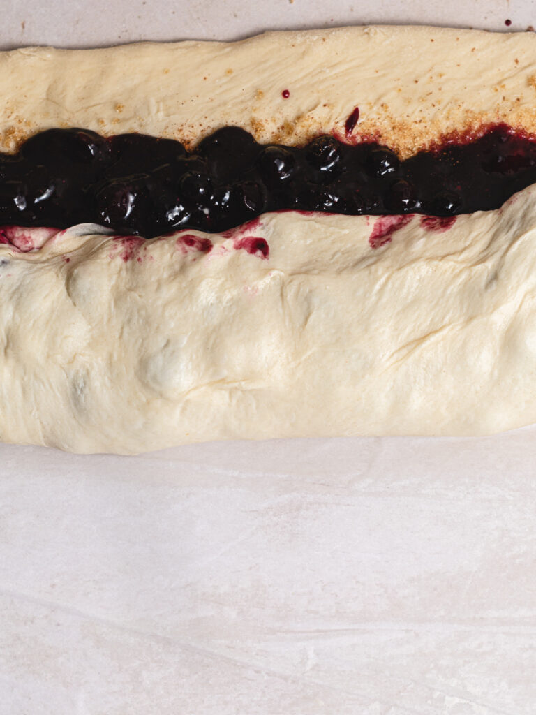 showing how to roll the vegan cinnamon rolls with blueberry